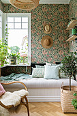 Summery conservatory with floral wallpaper and couch