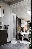 Grey bathroom on two levels with bathtub under sloping ceiling