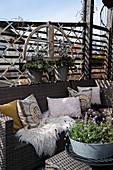 Kissen im Ethno-Stil und Felle auf dem Outdoorsofa
