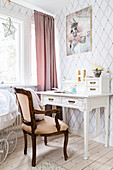 Vintage desk and antique armchair in bright room with diamond-patterned wallpaper