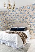 Double bed wiith headboard in romantic bedroom with floral wallpaper