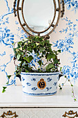 Ivy planted in ceramic pot on vintage chest of drawers below mirror on blue-and-white floral wallpaper
