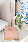 Book and vase of flowers on bedside table against blue-and-white floral wallpaper