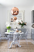 Round dining table and designer chairs in front of pale grey sideboard in open-plan kitchen