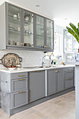 Kitchen counter with pale grey cupbards below wall cabinets with glass doors