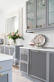 Pale grey kitchen counter, wall units with glass doors and vase of roses on sideboard