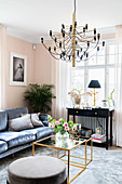 Dark velvet sofa, black console table, delicate coffee table with glass top and pouffe in pale pink living room