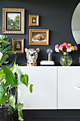 Ceramic leopard's head and vase of flowers on sideboard below gilt-framed pictures on dark wall