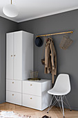 White wardrobe and classic chair below coat rack on grey wall