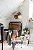 Metal, vintage-style child's bed below sloping ceiling