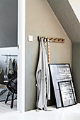 Row of coat pegs and pictures leaning against grey wall below sloping ceiling