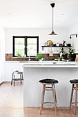 Kitchen counter used as partition in open-plan kitchen with rustic accessories