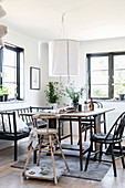 High chair, black chairs and bench around rustic dining table