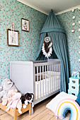Blue canopy with dreamcatcher above cot in nursery