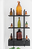 Old glass bottles on black wall-mounted shelves with drawers