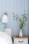 Bedside table next to double bed and wall lamp in bedroom with pale blue wall