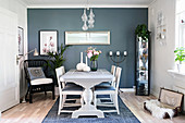 White table and chairs, display case and black wicker chair in dining area with matt blue accent wall