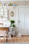 Rustic table in front of plate rack in kitchen-dining room with white door and wood-clad wall