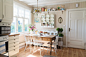 Rustic table, bench and chairs next to window in bright kitchen-dining room