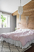 Bed with valance against board wall in Bohemian-style bedroom