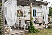 Gemütliche Terrasse mit Pergola und Holzboden am Haus