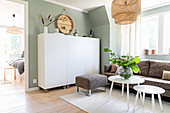 Bright, Scandinavian-style living room with grey-green wall
