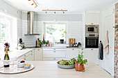 View over counter into white, Scandinavian-style kitchen