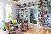 Living room with floor-to-ceiling shelves filled with books and ornaments