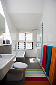 Bathtub and shower with glass screen in narrow bathroom
