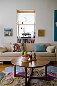 Ecru couch with scatter cushions and round table on colourful rug in living room