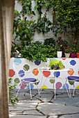 Delicate metal table and two chairs on terrace with multi-coloured mosaic wall