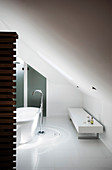 Free-standing bathtub with floor-mounted taps and bench in white designer bathroom with sloping ceiling