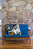 Wooden sofa with blue upholstery and colourful scatter cushion against stone wall