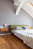 Double bed with green headboard and retro bedside table in bedroom with grey wall and white ceiling beams