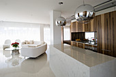 Fitted kitchen with marble counter and white designer sofa in front of window in open-plan interior