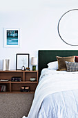 Double bed and shelf as bedside table in bedroom with white wall