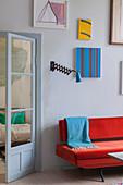 Red sofa below gallery of artworks next to glass door