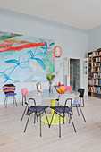 Round dining table and retro chairs in front of large painting