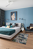 Double bed, mirrored bedside table and designer chair in bedroom with blue wall