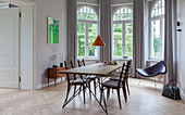 Dining table with slender lines and designer chairs in window bay