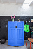 Blue half-height cabinet, shopping bags hung from wall hooks and black vase on floor against wall painted black and white