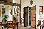 A pair of old, wooden, double Chinese doors in living room with dining table, wooden chairs and drawings on wall