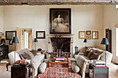 Danish linen sofas in living room with old oriental carpets and black standard lamps