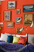 A collection of painted seascapes on red wall above day bed, the floor lamp is 1940s