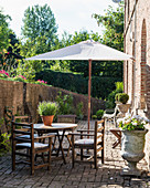 Teak furniture and stone urns on sunny bricked terrace with parasol