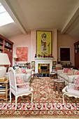 Wohnzimmer in Rosatönen mit antiken Polsterstühlen und Sofa am Kamin
