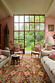 Couch and antique armchairs in front of floor-to-ceiling glass doors leading to garden in living room in shades of pink