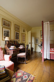Antique four-poster bed and bureau below gallery of pictures on yellow wall