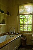 Antique, wood clad bathtub and wooden panelling in bathroom with lattice window