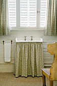 Antique sink with green, patterned curtain below under window